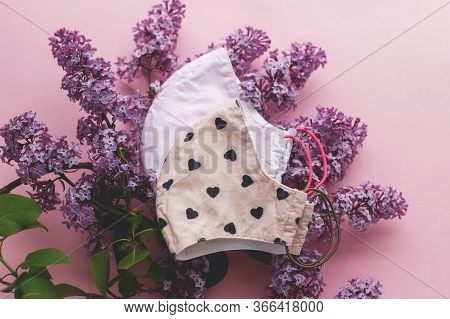 Zero Waste Lifestyle During Coronavirus Outbreak. Reusable Face Masks With Lilac Flowers On Pink Bac
