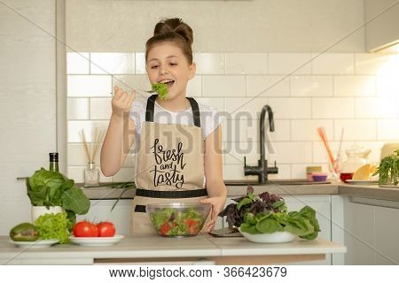 A Teenage Girl In Apron Prepared A Salad On Her Own In The Home Kitchen. She Holds A Bowl Of Cooked