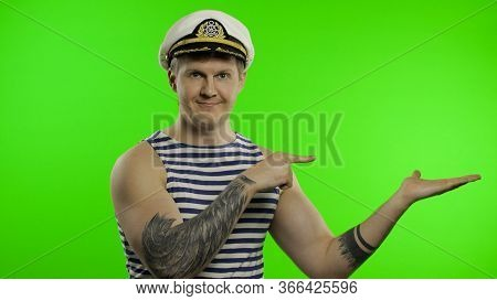 Young Muscular Sailor Man Pointing To Something With Hands. Seaman Guy Smiling In Sailors Vest. Stri