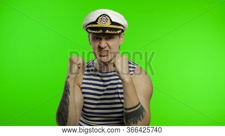 Young Muscular Sailor Man Is Angry And Shows Fists. Seaman Guy Smiling In Sailors Vest. Striped Navy