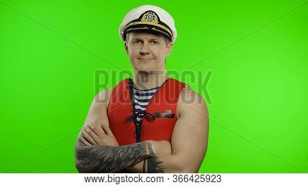Young Muscular Sailor Man Works As Lifeguard At Beach Arms Crossed, Looking At Camera. Seaman Guy Li