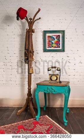 Green Wooden Vintage Side Table With Golden Antique Telephone Set, And Coat Hanger Stand With Red Fe