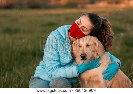 Portrait Of A Curly Young Woman Embracing Her Golden Retriever Dog In Spring Park. Young Woman Sitti