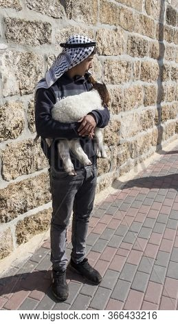 Bethlehem, Palestine - January 28, 2020: Boy With A Lamb In His Arms Standing On The Street In Bethl