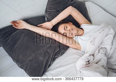 Attractive Smiling Young Woman Stretching In Bed Waking Up Alone, Awake After Healthy Sleep In Cozy