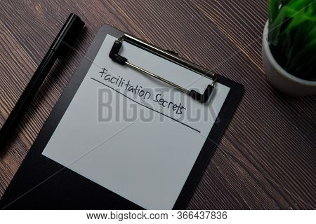 Facilitation Secrets Write On Paperwork Isolated On Wooden Table.