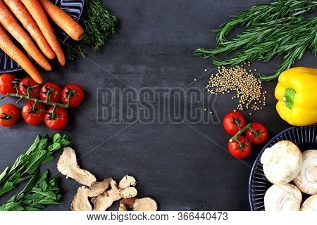 Top View Close Up Of Colorful Raw Vegetables On Black Table Surface. Ingredients For Vegetarian Cook