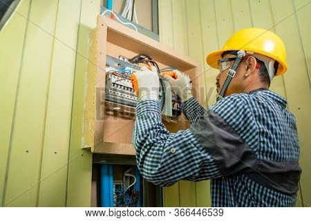 Electrician At Work At House,electrician Repairing Electrical Box With Pliers In Corridor Of A Resid