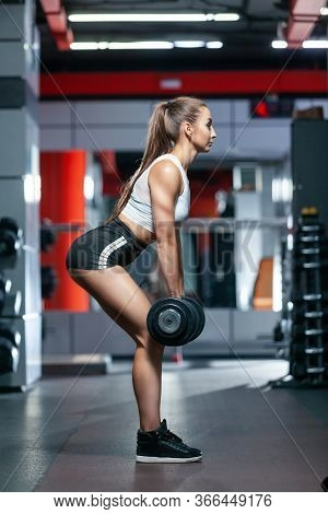 Side View Of A Muscular Slender Girl Performing An Exercise In The Gym Lifting Dumbbells