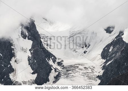 Atmospheric Minimalist Textured Alpine Landscape With Massive Glacier On Big Mountain In Low Clouds.