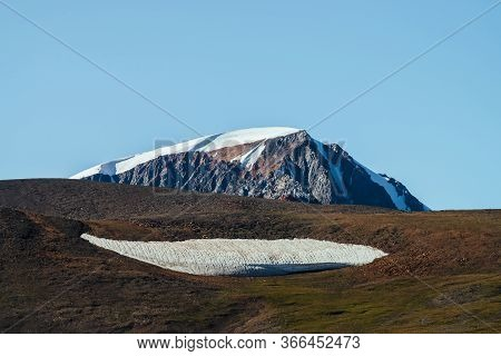 Giant Snowy Mountain Behind Green Hill With Big Piece Of Firn. Great Glacier Under Blue Sky. Wonderf