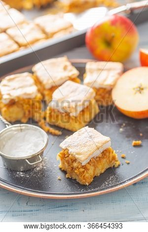 Five Cubes Of Apple Plie With A Cream Topping, Sugar Sieve And Half-cut Apple Next To It.