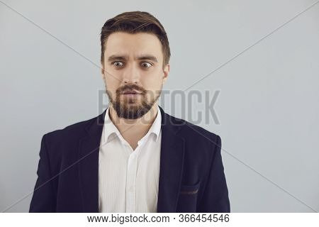 Puzzled Insecure Man In Casual Jacket On A Gray Background. Expression Of Emotion