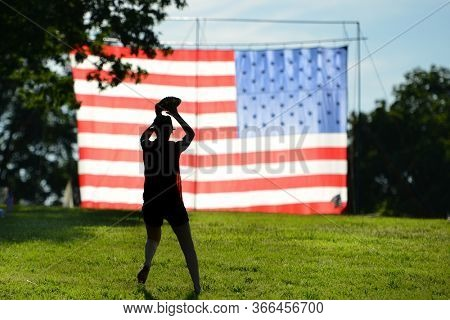 The Silhouette of  a football player hands the ball in front of huge United States National Flag erected in National Gardens Park in Washington DC during Memorial weekend