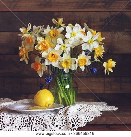 Bouquet Of Yellow And White Daffodils Of Different Varieties In A Glass Vase And Lemon. Simple And T