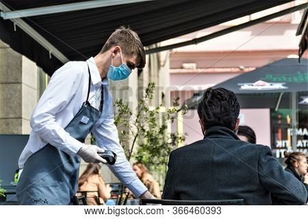Vilnius, Lithuania - May 15 2020: Waiter With A Mask And Gloves And Client At The Table Of An Outdoo