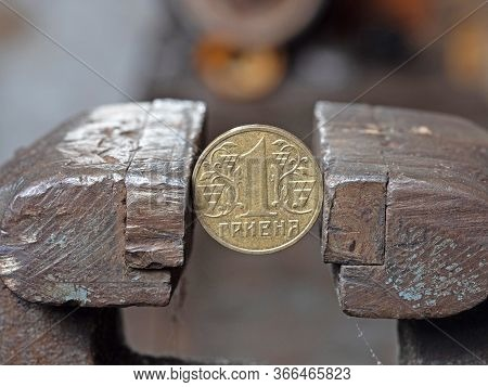 Hryvnya Coin Clamped In A Metal Vise. Currency And Ukrainian Economy Under The Onslaught, The Concep