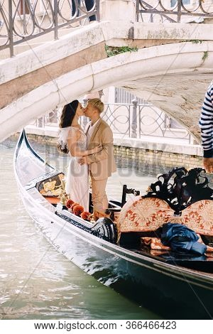 Italy Wedding In Venice. A Gondolier Rolls A Bride And Groom In A Classic Wooden Gondola Along A Nar