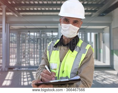 Civil Engineer Wears Protective Medical Mask Standing Against Concrete Wall At Construction Site