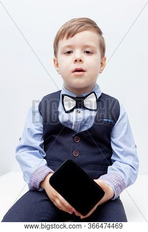 A Boy In A Shirt, Bow Tie, Vest And Trousers On A White Background Is Holding A Jewelry Box. Stylish