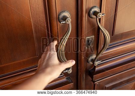 Hand Reaches For The Door Handle. Weathered Shabby Natural Wood Patterned Double Door With Shiny Vin