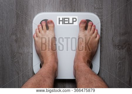 Top View Of The Feet Of A Barefoot Man Standing On Smart Scales, On Whose Balance It Is Written Help