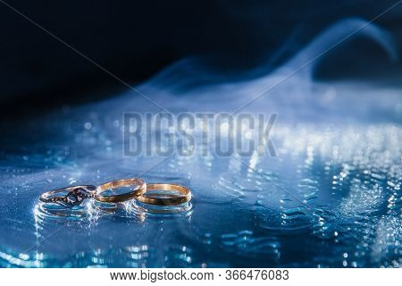 Wedding Ring. Three Gold Rings: An Engagement Ring And An Engagement Ring On The Mirror. A Blue Haze
