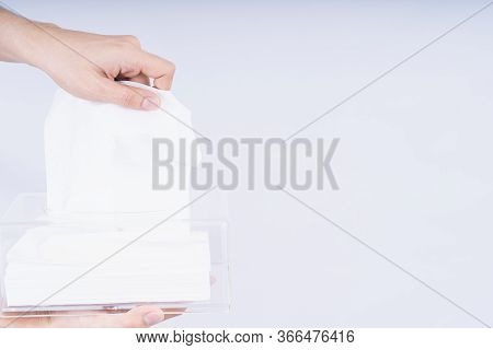 Delicate Male Hands Pulling A White Tissue Paper Out Of A Transparent Crystal Tissue Box.
