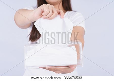 Delicate Female Hands Pulling A White Tissue Paper Out Of A Transparent Crystal Tissue Box.