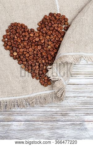 Gray Peas In Form Heart. Legumes Bean Seeds On Wooden Background With Copy Space.  Traditional Latvi
