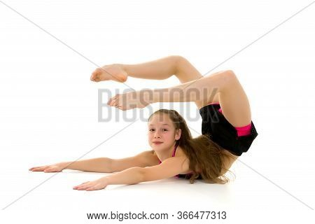 Gymnast Girl Lying On The Stomach Holding Up Her Legs, Flexible Girl Wearing Black Tank Top And Shor