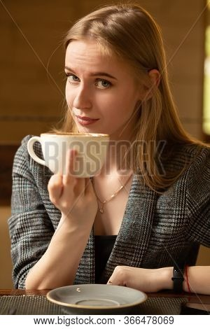 Ironical Young Woman With A Teacup Shows Fuck Gesture Looks In The Camera