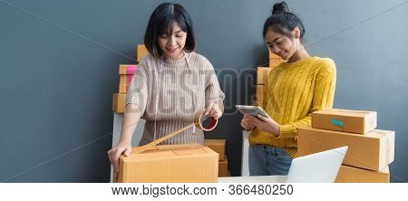 Women Packing Parcels With Sticky Tape, Entrepreneur Owner Using Smartphone Or Laptop Taking Receive