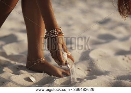 Hand Lifting Seashell From The Sand On The Beach Outdoors. Female Hand Holding Big Seashell. Summert