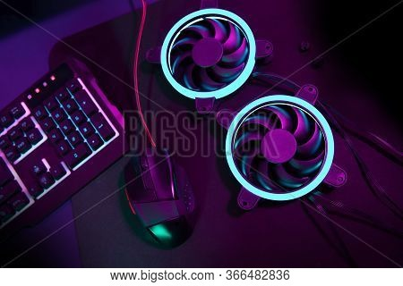 Modern Computer Fan With Blue Light Lying Next To Computer Gaming Mouse And Enlightened Gaming Keybo