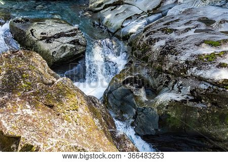 Fiordland National Park. A Stormy Stream Disappearing Into A Funnel. Funnel Chasm. Stream Among Ston