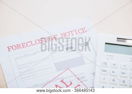 Top View Of Document With Foreclosure Lettering And Calculator On White