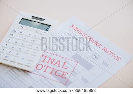 High Angle View Of Foreclosure And Final Notice Lettering With Calculator On White