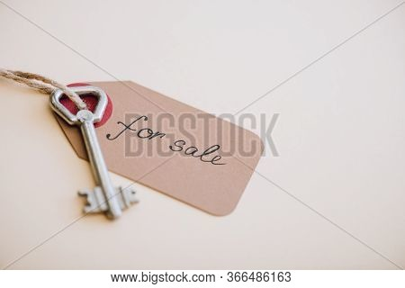 High Angle View Of Key With Trinket With For Sale Lettering On White Background