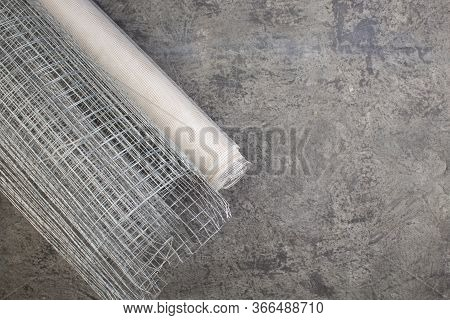 Roll Mesh For Plastering On The Gray Concrete Background. Copy Space. Top View.