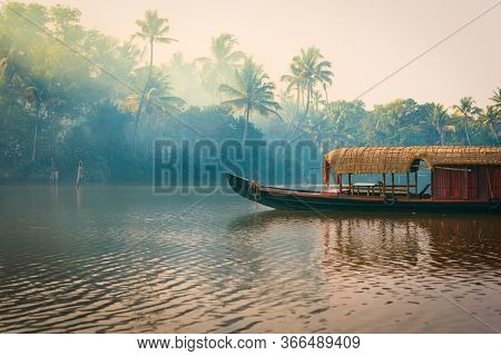 A Traditional House Boat Is Anchored On The Shores Of A Fishing Lake In The Palm Tree Jungle At Suns