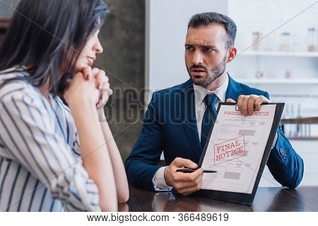 Tense Collector Pointing At Documents With Foreclosure And Final Notice Lettering And Looking At Wom