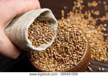 Buckwheat Groats (hulled Seeds) In Bowl , Hand With Burlap Bag, Closeup. Ingredient In Breakfast Foo