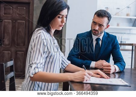 Woman Writing In Documents Near Tense Collector At Table In Room