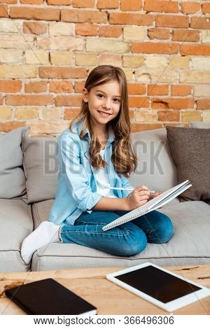 Happy Kid Sitting On Sofa And Writing In Notebook Near Digital Tablet With Blank Screen