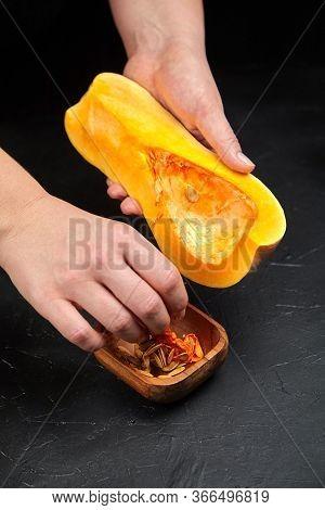 Butternut Squash, Woman Picks Pumpkin Seeds. Female Hands, Wooden Bowl On Black Background, Closeup.