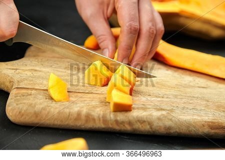Butternut Squash Pieces On Wooden Chopping Board On Black Background. Female Hands With Steel Knife,