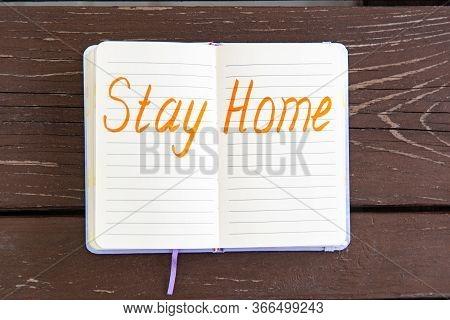 Coronavirus Stay Home Warning Written In Bright Orange Felt-tip Pen In Notepad. Brawn Wooden Table.
