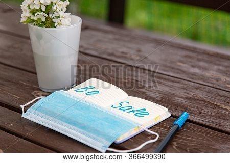 Coronavirus Be Safe Warning Written In Bright Blue Felt-tip Pen In Notepad With Medical Mask. Brawn