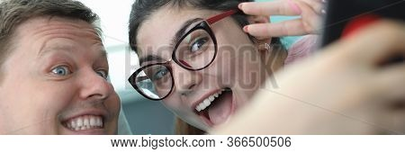 Close-up Of Smiling Man Holding Smartphone. Happy Woman And Ill Male Looking At Mobile With Happines